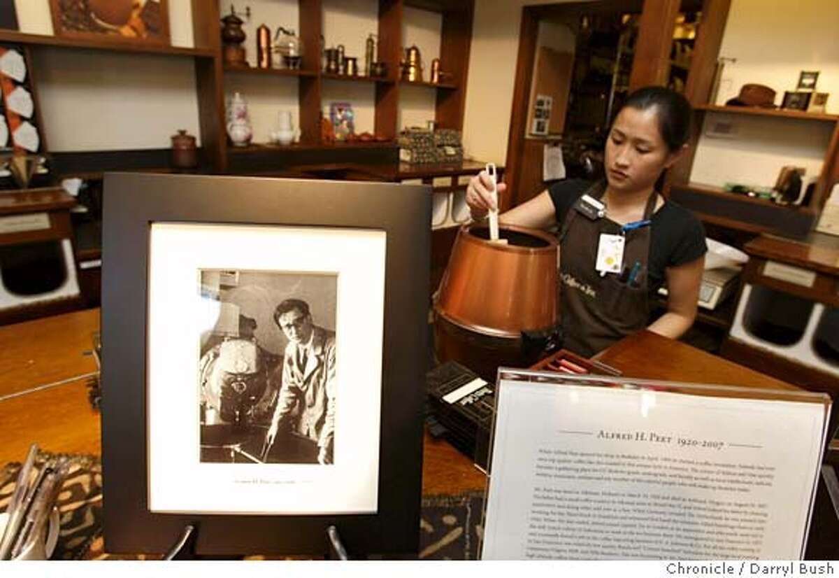 peetscoffee_db_004.JPG Manager, Fauchon Hong, grinds coffee in background near a photo and bio of Peet's Coffee founder, Alfred H. Peet, foreground, at Peet's Coffee & Tea on Vine St. in Berkeley, CA, on Friday, August, 31, 2007. photo taken: 8/31/07 Photo by Darryl Bush / Special to the Chronicle ** Fauchon Hong (cq) MANDATORY CREDIT FOR PHOTOGRAPHER NO SALES-MAGS OUT
