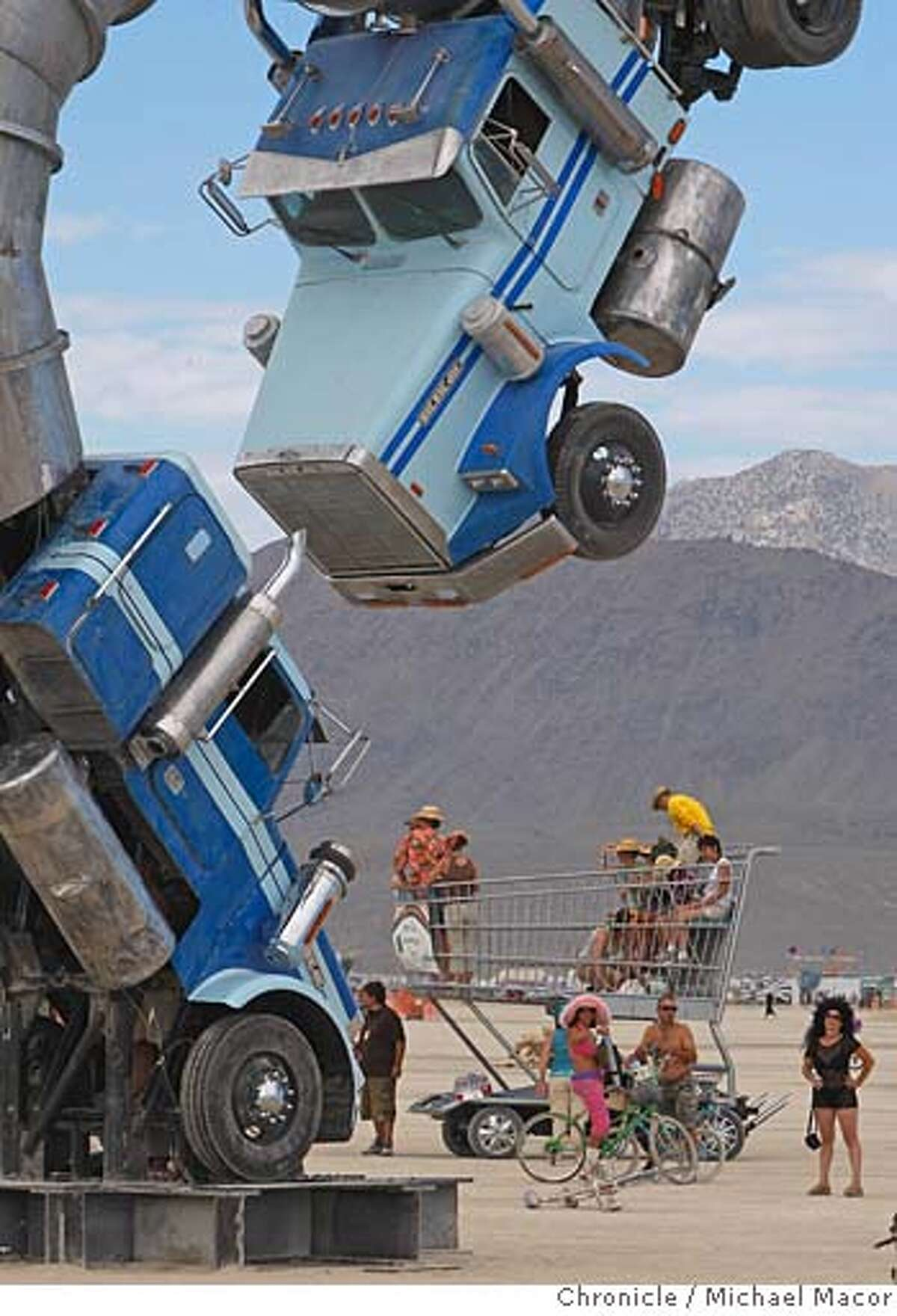 burningman_040_mac.jpg Artpiece, Big Rig Jig by Mike Ross combines a couple of BIg Rig semi trucks into art. A very large shopping cart stops nearby to get a look of the artpiece. Burning Man 2007. Photographed in, Black Rock City, Nv, on 8/31/07. Photo by: Michael Macor/ The Chronicle