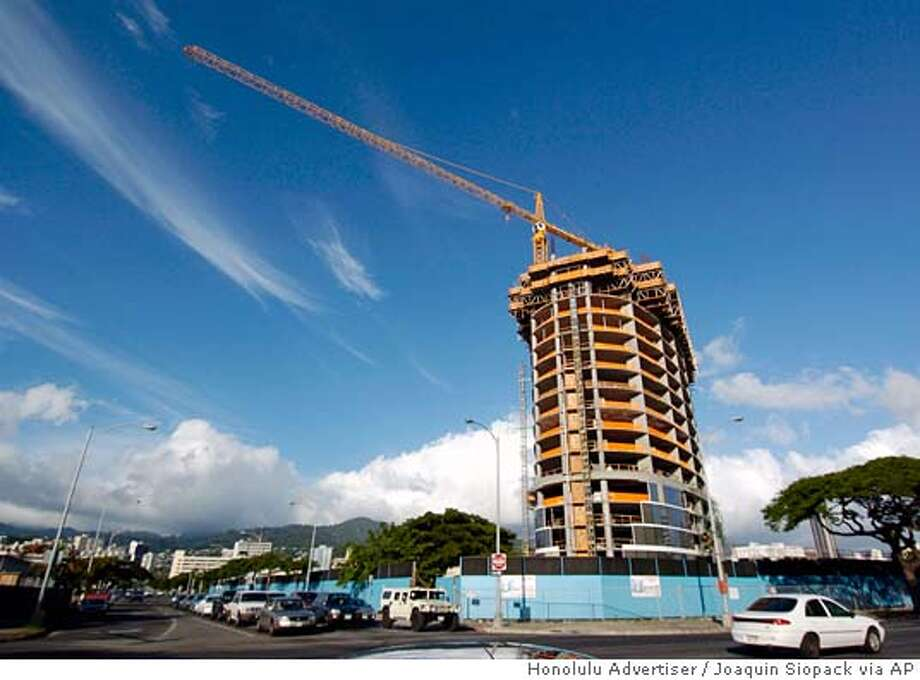 ** ADVANCE FOR WEEKEND EDITIONS NOV. 5-6 ** Construction continues at Moana Pacific condominiums in the Kakaako district of Honolulu, on Oct. 27, 2005. With buyer demand driving Hawaii's housing boom, developers have created a bulge in this area near downtown Honolulu, where there are plans for 14 new residential towers with about 4,000 units. The area's condominium development pipeline has gotten so fat that it is eliciting concern about overbuilding. (AP Photo/Honolulu Advertiser, Joaquin Siopack) THE STAR-BULLETIN OUT ADVANCE FOR NOV. 5-6, OCT. 27, 2005 PHOTO Photo: JOAQUIN SIOPACK