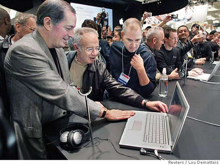 (L-R) Intel CEO Paul Otellini, former Intel CEO Andy Grove and Apple CEO Steve Jobs look at the new MacBook Pro laptop computer at the Macworld Conference and Expo in San Francisco January 10, 2006. The MacBook Pro, which Jobs introduced during his keynote address, uses new two-brained chips from Intel, the first Intel chips to be used in a Mac. REUTERS/Lou Dematteis Photo: LOU DEMATTEIS