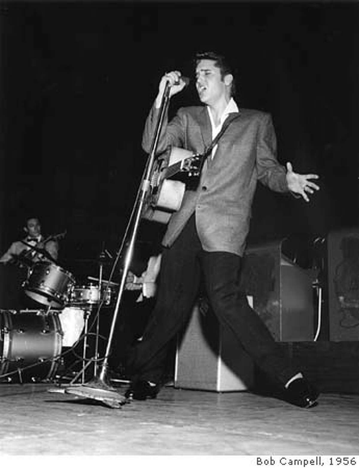ELVIS 1/B/24SEP97/DD/BC--Elvis Presley in Oakland in 1956. CHRONICLE PHOTO BY BOB CAMPBELL Ran on: 01-09-2005 Elvis entertains his fans during a 1956 show in Oakland.