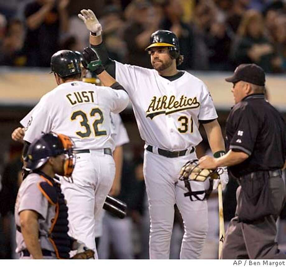 Oakland Athletics' Mike Piazza (31) congratulates Jack Cust (32) after Cust homered off Detroit Tigers' Virgil Vasquez in the fourth inning of a baseball game Friday, Aug. 31, 2007, in Oakland, Calif. (AP Photo/Ben Margot) Photo: Ben Margot