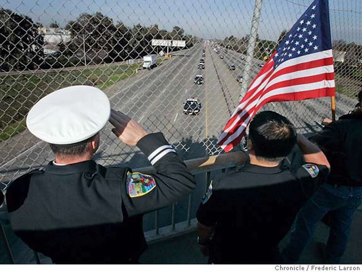 {object name} Palo Alto firefighters (R-L) Jon Matsumto and Randy Fisher salute a fallen hero on a highway overpass as the funeral procession for slain East Palo police Officer Richard May was escorted by hundreds of officers when south bound from Menlo Park to downtown San Jose. 1/12/06 Frederic Larson