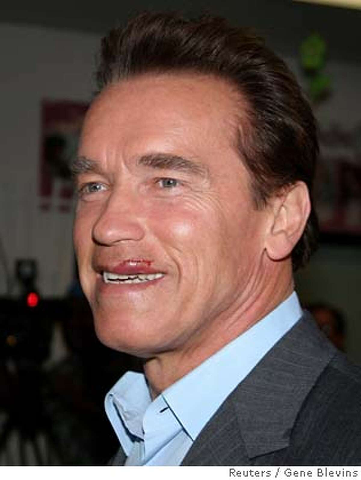 California governor Arnold Schwarzenegger smiles during a news conference at the Northeast Valley Health Corp in North Hollywood, California January 9, 2006. Schwarzenegger was back at work Monday after suffering a minor motorcycle accident that required a hospital visit to receive 15 stitches to treat a cut lip, his office said. REUTERS/Gene Blevins 0