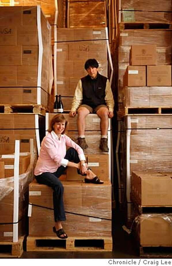 KINGSTON17_051_cl.JPG  Story about Kingston Family Vineyards. Their wines and vineyard is in Chile and import their wines to the United States. Photo of Courtney Kingston (seated below) and Byron Kosuge (top), the winemaker. They are with almost all of their shipment of wine from Chile located in a warehouse in Napa.  on 8/27/07 in Napa. photo by Craig Lee / The Chronicle MANDATORY CREDIT FOR PHOTOG AND SF CHRONICLE/NO SALES-MAGS OUT Photo: Photo By Craig Lee