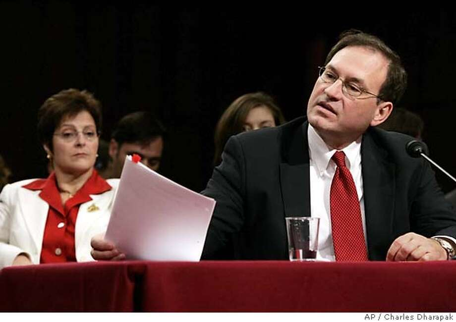 Supreme Court nominee Samuel Alito looks at papers about Vanguard Group as he is questioned by Sen. Edward Kennedy, D-Mass., about avoiding conflicts of interest on the fourth day of his Senate Judiciary Committee confirmation hearings on Capitol Hill in Washington, Thursday, Jan. 12, 2006. At left, Alito's wife, Martha-Ann. (AP Photo/Charles Dharapak) Photo: CHARLES DHARAPAK