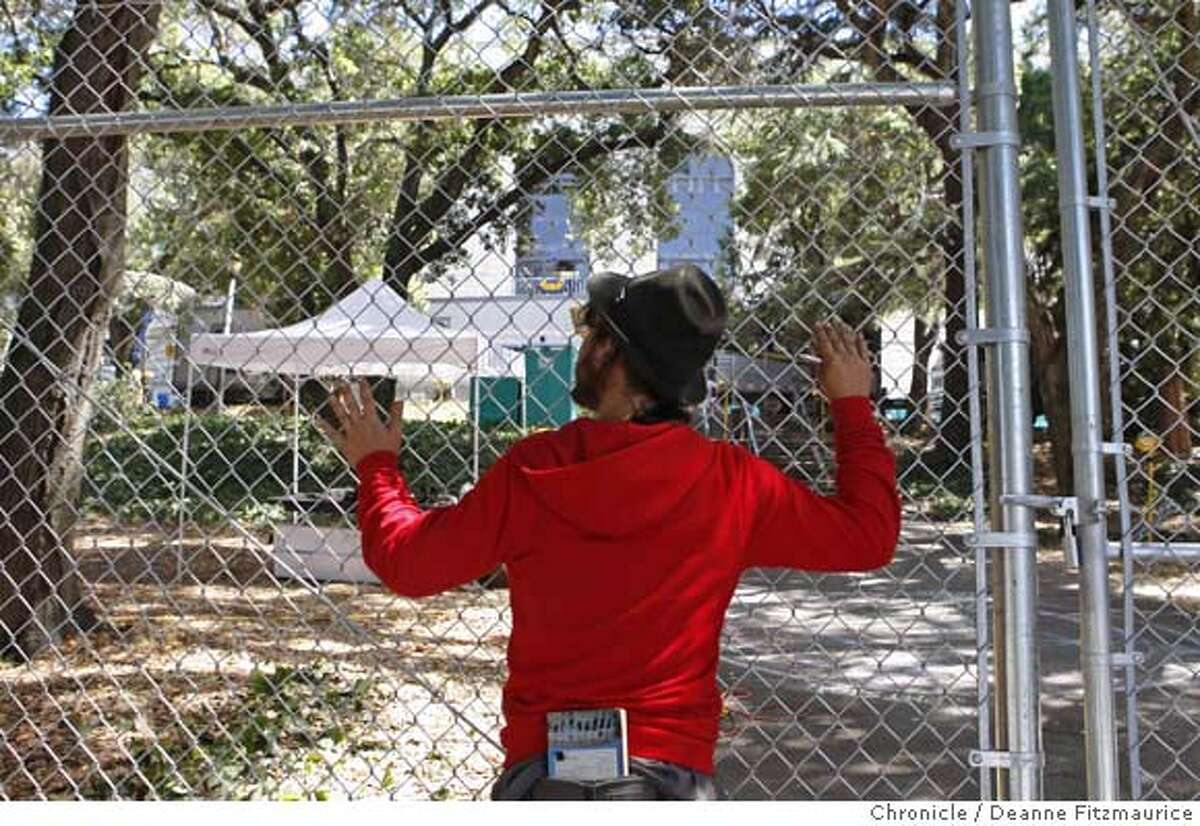 treesitters31_034_df.jpg Matthew Ryan, a supporter of the tree sitters looks through the newly constructed fence. The tent inside the fence is where security oficers are set up. Tree sitters and their supporters are trying to protect a grove of trees from being torn down from in front of Memorial Stadium at UC Berkeley. Photographed in Berkeley on 8/30/07. Deanne Fitzmaurice / The Chronicle Mandatory credit for photographer and San Francisco Chronicle. No Sales/Magazines out.