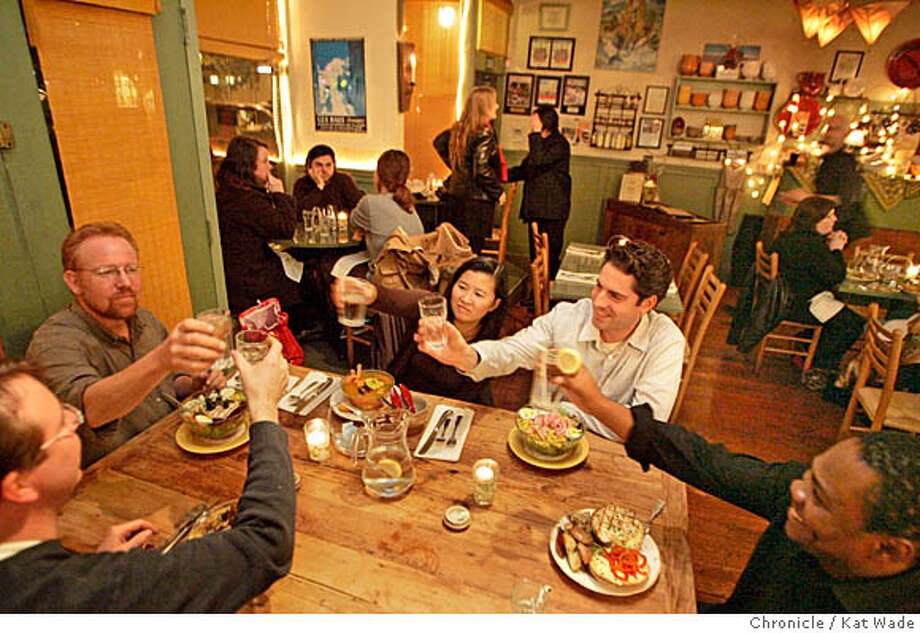 On 12/15/05 in Berkeley (L to R) Mark Seka, from El Cerrito, Matt Cantor, from Berkeley, chi and Chris Sullivan of Kensington, toast during a birthday dinner for Foley Laiyemo, (right) from Pittsburg during time at La Note, a provencal restaurant on Shattuck Avenue that serves dinner three nights a week. In the background (Left) Berkeley roommates (L to R) Nicole Drake, Zack Vieira, and Michelle Scheurich dine at one of the window tables.  Kat Wade/The Chronicle Photo: Kat Wade