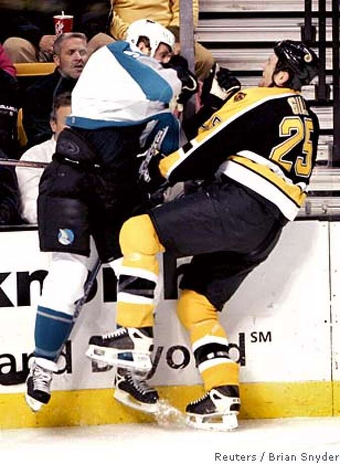 The San Jose Sharks' Joe Thornton (L) checks the Boston Bruins' Hal Gill in the first period of their NHL game in Boston, Massachusetts January 10, 2006. Thornton, who was traded to the Sharks from the Bruins earlier in the season, received a game misconduct penalty for the hit. REUTERS/Brian Snyder Photo: BRIAN SNYDER