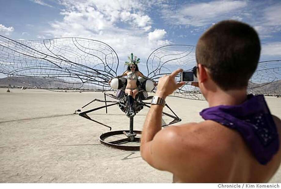 """BURNINGMAN30_059_KK.JPG  Eric Krasavage (R) photographs Marissa Price on Bryan Tedrick's """"Damsel Fly"""" Thursday at Burning Man Festival at Black Rock City, near Gerlach, Nevada. Damsel Fly by Bryan Tedrick is a 30-foot steel and wood sculpture. The sculpture can spin around and is complete with a seat between the eyes for those who wish to ride. Photo by Kim Komenich/The Chronicle  **Eric Krasavage, Marissa Price, Bryan Tedrick MANDATORY CREDIT FOR PHOTOG AND SAN FRANCISCO CHRONICLE. NO SALES- MAGS OUT. Photo: Kim Komenich"""