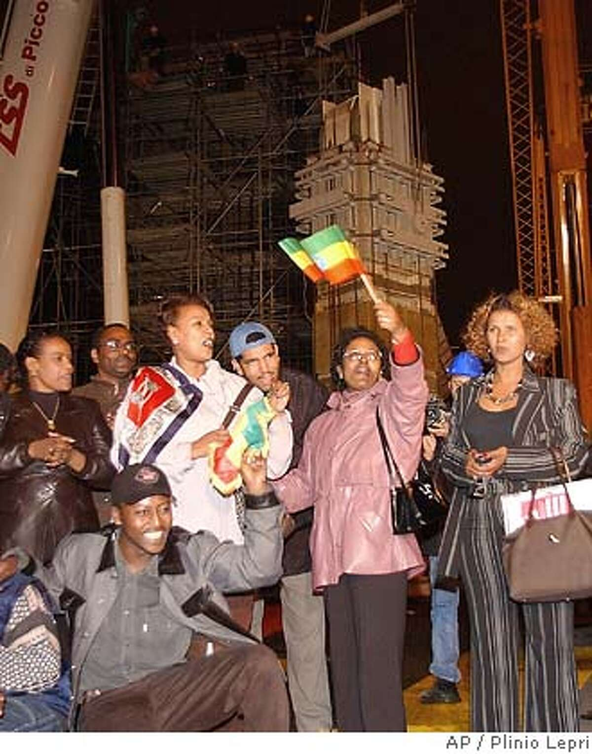 Members of the Ethiopian community in Rome, cheer after the removal of the top part - about seven meters (yards) long and weighing 40 tons in background - of the 1,700-year-old Axum Obelisk, in central Rome, in the early evening Friday Nov. 7, 2003. Eventually the full 24-meter (82 foot)-structure is to return to Ethiopia, decades after the monument was taken by Fascist dictator Benito Mussolini's forces. The Italian government decided last year to start procedures to return the prized symbol after decades of Ethiopian officials demanding it back. (AP Photo/Plinio Lepri) Ethiopian Italians cheer in central Rome after the top of the Axum Obelisk is removed. The 7-meter-long piece of the 1,700-year-old treasure weights 40 tons. Photo caption italy09_PH11068076800APMembers of the Ethiopian community in Rome, cheer after the removal of the top part - about seven meters (yards) long and weighing 40 tons in background - of the 1,700-year-old Axum Obelisk, in central Rome, in the early evening Friday Nov. 7, 2003. Eventually the full 24-meter (82 foot)-structure is to return to Ethiopia, decades after the monument was taken by Fascist dictator Benito Mussolini's forces. The Italian government decided last year to start procedures to return the prized symbol after decades of Ethiopian officials demanding it back. (AP Photo-Plinio Lepri) Ethiopian Italians cheer in central Rome after the top of the Axum Obelisk is removed. The 7-meter-long piece of the 1,700-year-old treasure weighs 40 tons. CAT