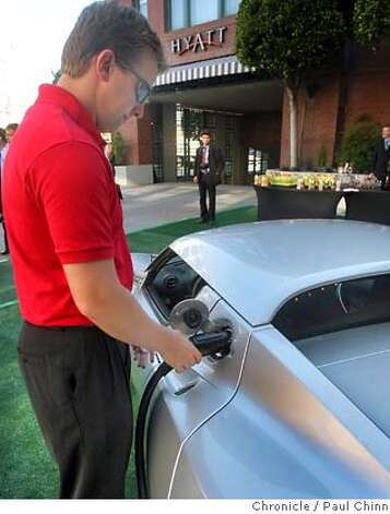 Test engineer Andrew Simpson plugs in the Tesla Roadster electric car for a quick recharge before it was unveiled at a Hyatt Hotel in San Francisco, Calif. on Wednesday, August 29, 2007. The hotel chain announced plans to install several power stations at select hotels that will recharge the $98,000 vehicle.  PAUL CHINN/The Chronicle  **Andrew Simpson MANDATORY CREDIT FOR PHOTOGRAPHER AND S.F. CHRONICLE/NO SALES - MAGS OUT Photo: PAUL CHINN
