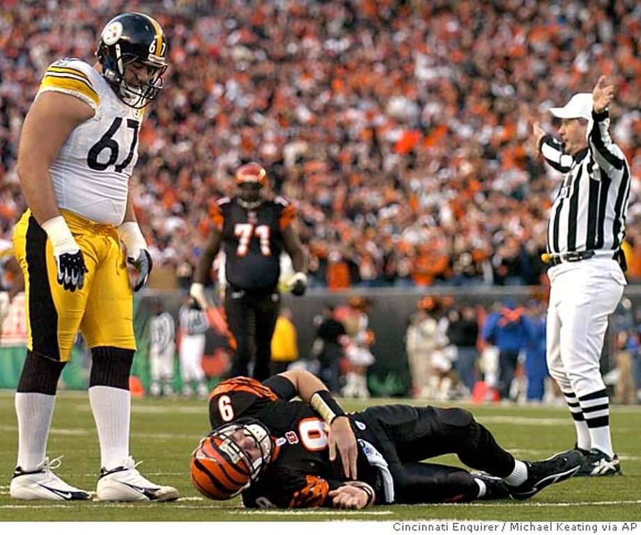 Pittsburgh Steelers' Kimo von Oelhoffen (67) stands over Cincinnati Bengals quarterback Carson Palmer (9) after Palmer injured his knee in the first half of their NFL playoff football game, Sunday, Jan. 8, 2006, in Cincinnati. (AP Photo/Michael Keating,Cincinnati Enquirer) Photo: MICHAEL KEATING