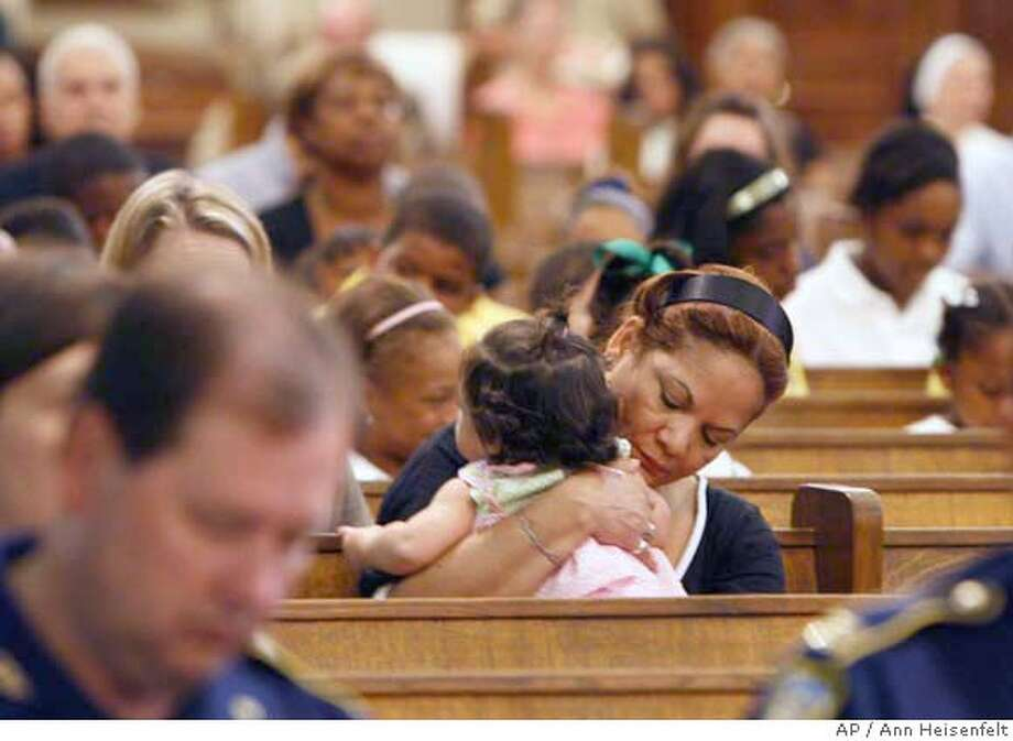 Maria Nelson holds her daughter, Meredith, as she attends a service commemorating the second anniversary of Hurricane Katrina at St. Louis Cathedral in New Orleans, Wednesday, Aug. 29, 2007. Nelson lost her home in the Lakeview area during the storm. (AP Photo/Ann Heisenfelt) Photo: Ann Heisenfelt