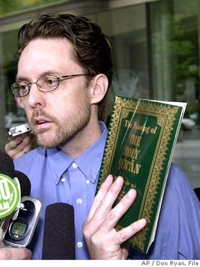 """**FILE**Brandon Mayfield holds up a book titled """"The Meanining of the Holy Quaran"""" outside the federal courthouse in Portland, Ore., after he was released from custody Thursday, May 20, 2004. The Justice Department' on Friday, Jan. 6, 2006, faulted the FBI for sloppy work in mistakenly linking Mayfield, an Oregon lawyer and a Muslim convert, to the 2004 Madrid train bombings but said the government did not misuse the anti-terror Patriot Act against him. (AP Photo/Don Ryan) Photo: DON RYAN"""