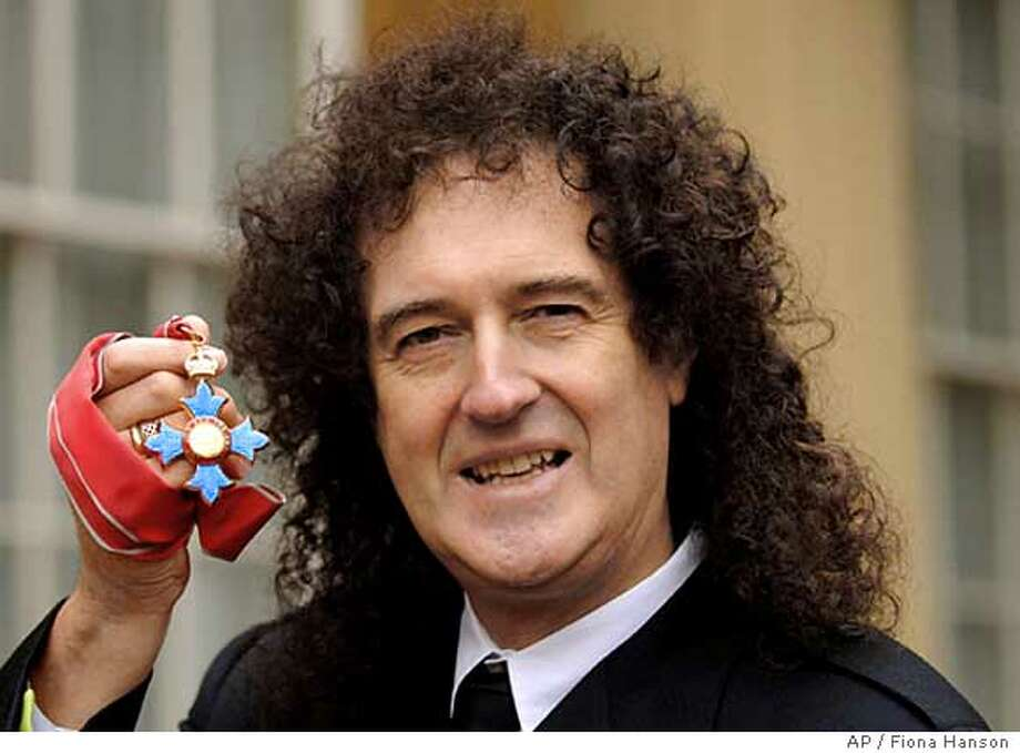 Queen guitarist Brian May hold the insignia of his Commander of the British Empite award, after collecting it from Britain's Queen Elizabeth II during an investiture ceremony at Buckingham Palace in London, Tuesday Dec. 6, 2005.(A_P Photo/Fiona Hanson, pool) POOL Photo: FIONA HANSON