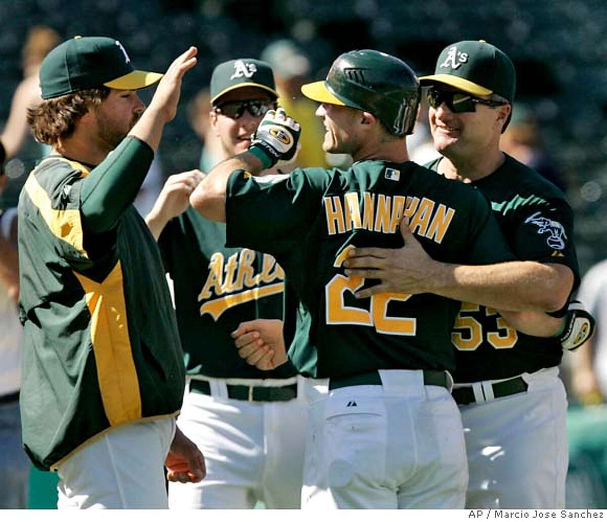 Oakland Athletics' Jack Hannahan, center right, is congratulated by manager Bob Geren, right, and Mike Piazza, left, after driving in the game-winning run with a single off Toronto Blue Jays pitcher Scott Downs in the 11th inning of a baseball game in Oakland, Calif., Wednesday, Aug. 29, 2007. Oakland won 5-4. The other person is not identified. (AP Photo/Marcio Jose Sanchez) EFE OUT