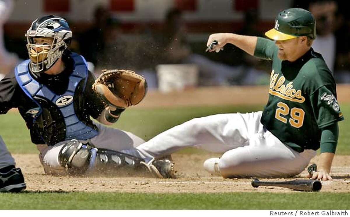 Oakland Athletics base runner Dan Johnson (R) slides safely into home in the third inning as the ball gets past Toronto Blue Jays catcher Gregg Zaun during their MLB American League game in Oakland, California August 29, 2007. REUTERS/Robert Galbraith (UNITED STATES)