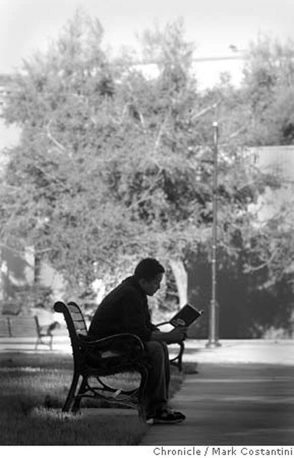 """Campusnotes_087 1/4/06 At San Jose State University, on a sunny afternoon, Aerospace Engineering major Justin Custodio, a sennior sits in a shady spot and reads """"The Little Prince"""". Photo for Campus Notes education page in 1/8/06 Sunday paper. Event on 1/4/06 in {San Josw), {CA}. Photography by Mark Costantini / San Francisco Chronicle Photo: MARK COSTANTINI"""