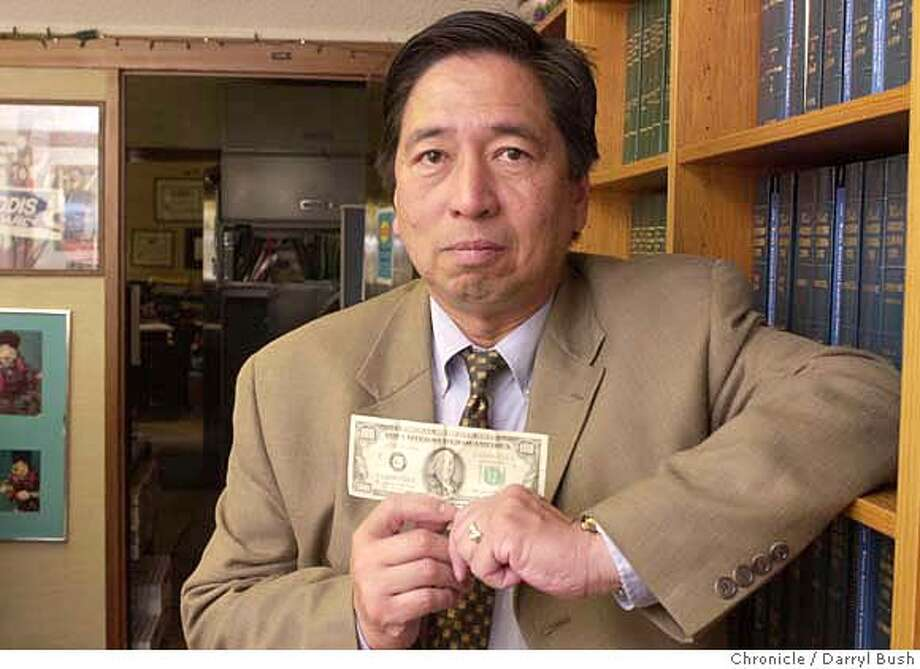 RODIS-C-22FEB03-MT-DB Attorney Rodel E. Rodis holds the 1984 one-hundred dollar bill in his office in San Francisco. He was arrested for using a counterfeit bill despite the fact the bill (shown here) was legal tender.Chronicle Photo by Darryl Bush Ran on: 10-28-2004  Natalie Berg Photo: Darryl Bush