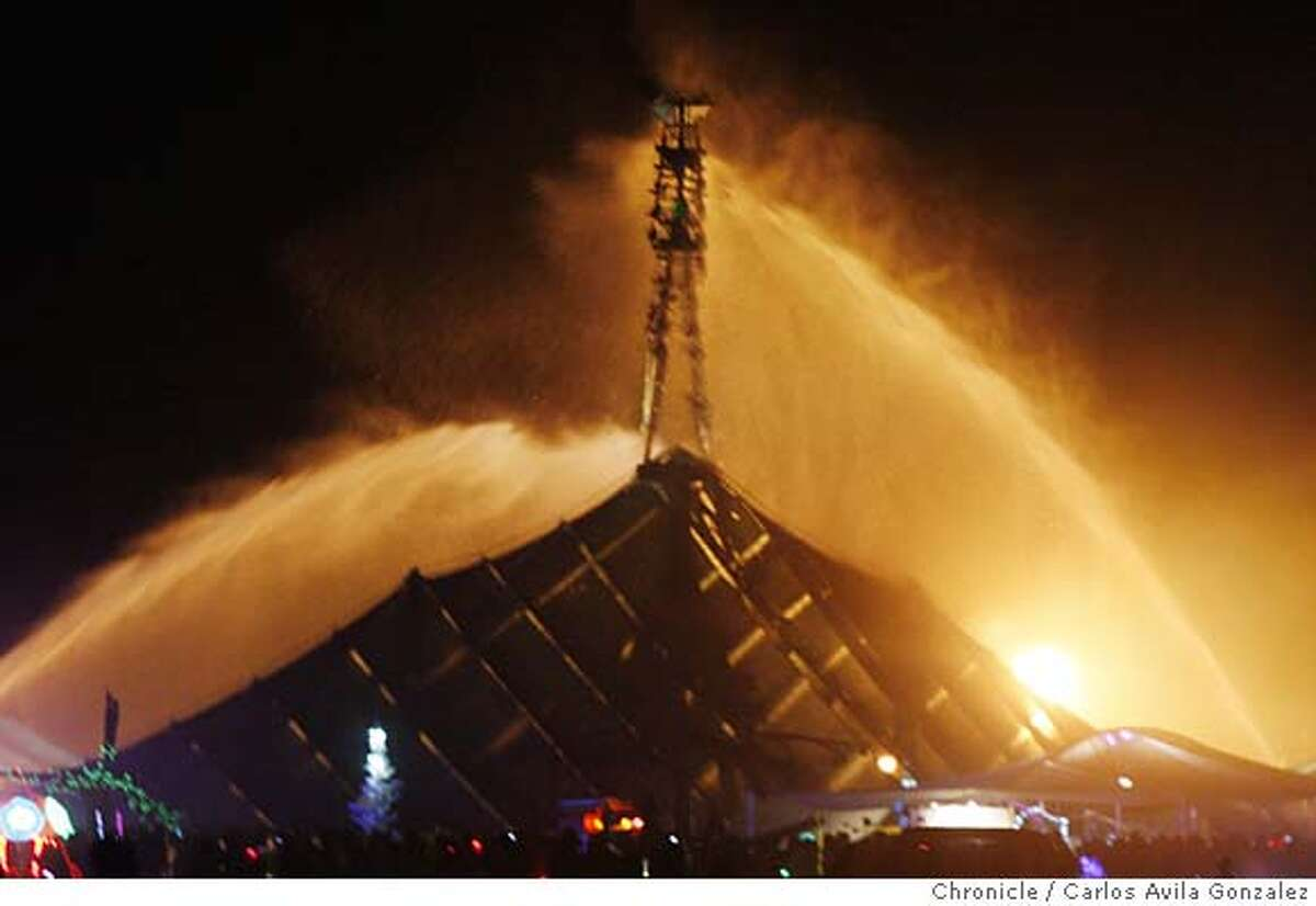 Burning_Man_0002_CAG.JPG Firefighters blast water at the man to extinguish an attempted arson on the fire festival icon. The art structure known as The Man, the center of the Burning Man Festival in the Nevada desert, was set afire on Tuesday morning, August 28, 2007. An unknown man allegedly climbed the structure from within, and was reported to have placed an object in the leg of The Man which then ignited and set the wooden structure burning five days before it was officially supposed to be burned. The suspect was taken into custody by Bureau of Land Management rangers patrolling the festival. Photo by Carlos Avila Gonzalez/The Chronicle Photo taken on 8/28/07, in Black Rock City, Nv, USA. **All names cq (source)