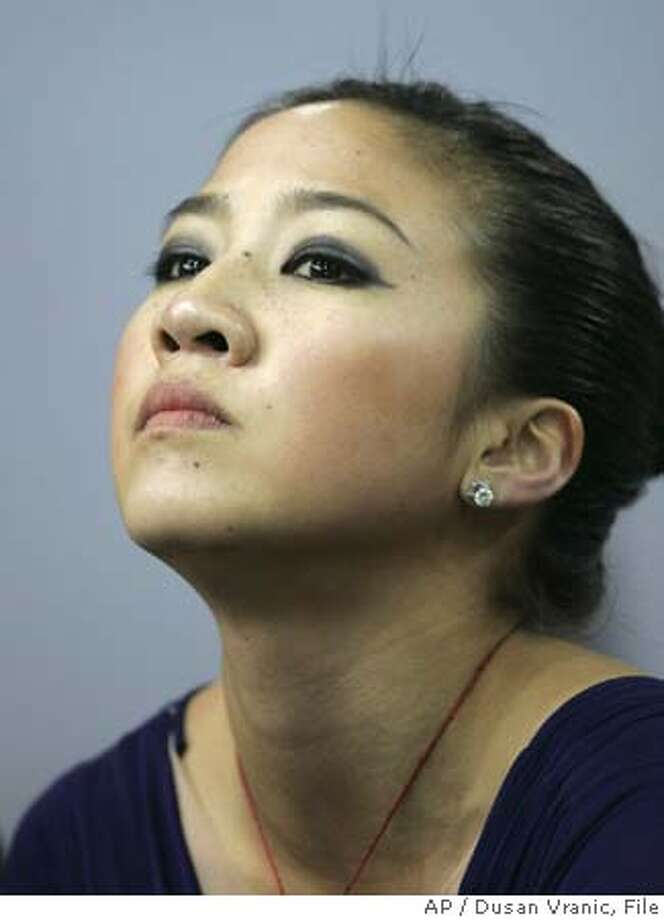 ** FILE ** Michelle Kwan of the United States watches her marks during the ladies qualifying free skating at the World Figure Skating Championships in Moscow, in this March 16, 2005 photo. Kwan withdrew from the U.S. Figure Skating Championships on Wednesday with a groin injury but will petition for a spot on the Olympic team that leaves for Turin, Italy, next month. Instead, she hopes to get one of the three spots being contested by petitioning U.S. Skating. The nine-time national champion and five-time world gold medalist missed nearly all of this season with injuries, but was expected to skate next week in St. Louis, where the team will be picked. (AP Photo/Dusan Vranic) A MARCH 16, 2005 FILE PHOTO Photo: DUSAN VRANIC