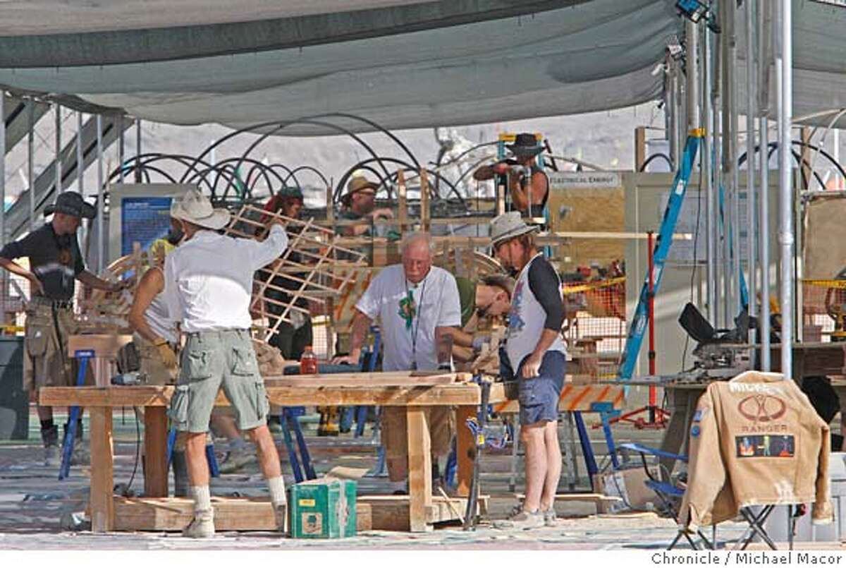 """burningman_014_mac.jpg Workers busy with rebuilding of the """"Green Man"""" after an early Tuesday morning arson attack destroyed the centerpiece structure. Burning Man 2007. Photographed in, Black Rock City, Nv, on 8/29/07. Photo by: Michael Macor/ The Chronicle"""