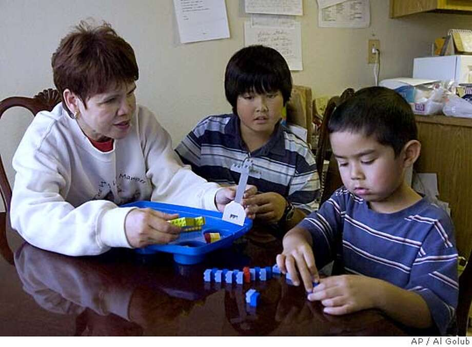 Libbey Holden plays with her grandsons, 10-year-old Joshua Calero, left, and 5-year-old Jason Calero, in her apartment Wednesday, Jan. 4, 2006, in Manteca, Calif. The boys' parents, Jacob Calero and Michelle De la Vega, left Calero's sons at their San Ramon, Calif., home early Friday while the newlyweds headed out of town for a five-day trip, police said. (AP Photo/Al Golub) Photo: AL GOLUB