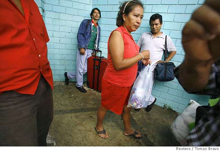 Residents wait for information about Hurricane Dean outside an auditorium which was used as a shelter in Poza Rica, Mexican state of Veracruz, August 22, 2007. Hurricane Dean ripped into Mexico's Gulf coast on Wednesday with screaming winds and torrential rain that flooded towns, forced thousands into shelters and worried world oil markets. REUTERS/Tomas Bravo (MEXICO) Photo: TOMAS BRAVO