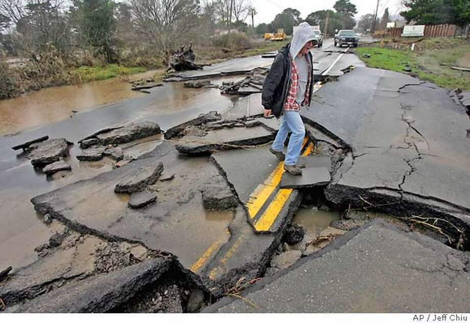 Daniel Dallara looks over the damage caused by the storm on Highway 12, which caused a closure near the junction with Highway 121, in Sonoma County, Calif., Sunday, Jan. 1, 2006. Northern California residents braced for a second storm to hit the region Sunday, a day after the first sent rivers rising into cities and mud sliding into homes and across highways. (AP Photo/Jeff Chiu) Photo: JEFF CHIU