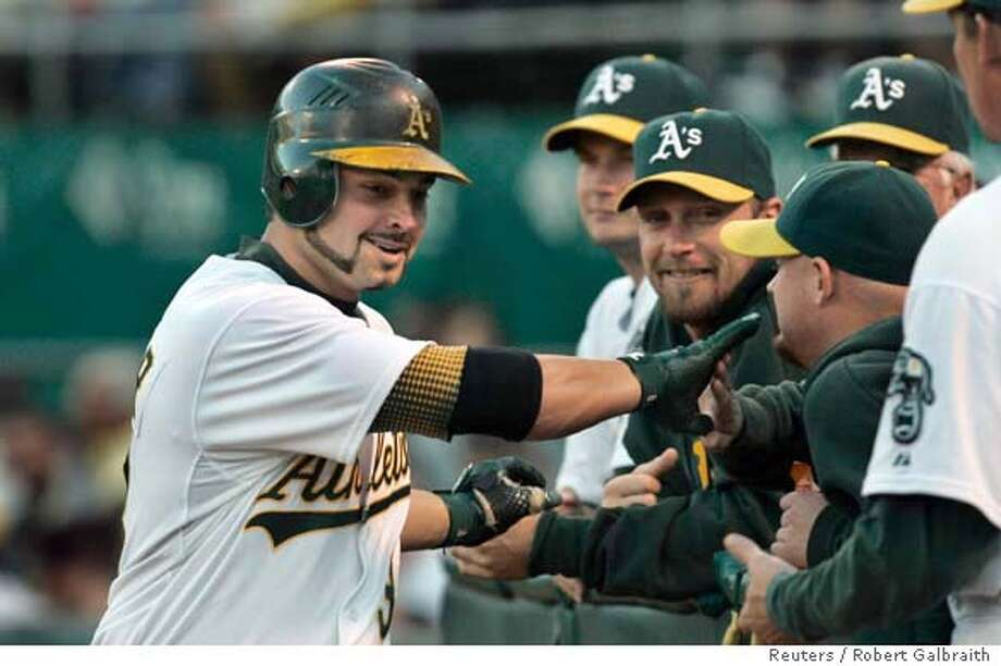 Oakland Athletics Nick Swisher (L) in congratulated by teammates after hiting a solo home run in the first inning against the Toronto Blue Jays during their MLB American League game in Oakland, California August 27, 2007. REUTERS/Robert Galbraith (UNITED STATES) Photo: ROBERT GALBRAITH