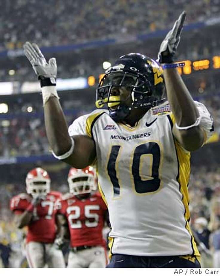 West Virginia running back Steve Slaton (10) reacts after scoring his second 52-yard touchdown run in the game at the Georgia Dome in Atlanta on Monday, Jan. 2, 2006. At left is Georgia's Tra Battle (25) and Greg Blue (17). (AP Photo/Rob Carr) Photo: ROB CARR