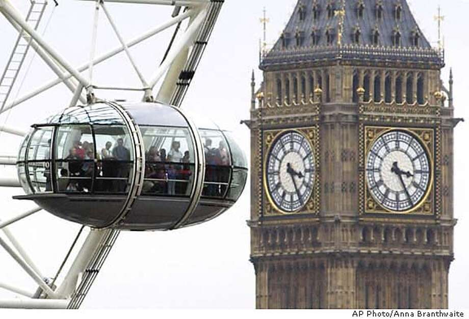 The London Eye, a large rotating ferris wheel, gives people a bird's eye view of London including the clock tower of the Houses of Parliament, background, Aug. 1, 2003 (AP Photo/Anna Branthwaite) Photo: ANNA BRANTHWAITE