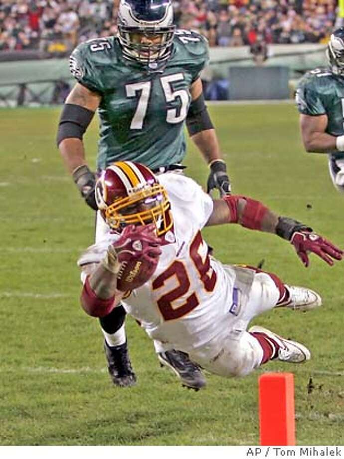 Washington Redskins running back Clinton Portis (26) dives to end a 22-yard run for a touchdown against the Philadelphia Eagles in the fourth quarter of their NFL football game Sunday, Jan. 1, 2006, in Philadelphia. Behind Portis is Eagles tackle Hollis Thomas.(AP Photo/Tom Mihalek) Photo: TOM MIHALEK