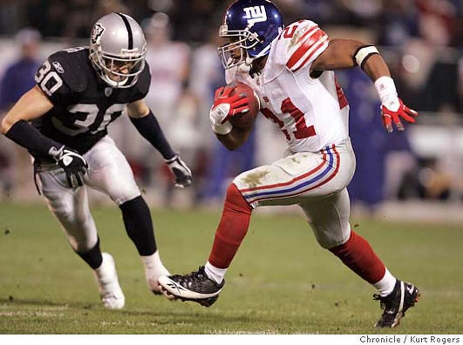 Tiki Barber runs past Stuart Schweigert on a 95 yard run in the second quarter.  The Oakland Raiders vs the New York Giants Kurt Rogers Oakland SFC  The Chronicle Photo: Kurt Rogers