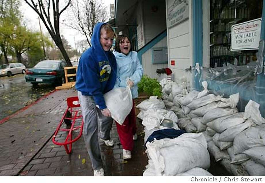"flood197_cs.jpg  Event on 12/29/03 in Napa. Jessica Prince, 10 (red pants, light blue jacket) and Brooke Borges, 11 (dark blue hooded sweatshirt) carry sand bags as they help protect the Glamorama Hair Salon, 1016 Clinton Street, Napa, owned by Brooke's mother Terra Borges. Other residents of Napa also prepared for possible flooding if the Napa River overflows its banks. Brooke has helped out in previous floods. ""She thinks this is fun,"" said her mother Terra. Terra Borges can be reached at 707-255-0633. Chris Stewart / The Chronicle Photo: Chris Stewart"