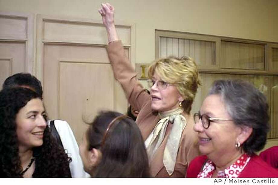 Actress Jane Fonda rise her arm after a meeting with women activists in Guatemala City Sunday Nov. 30, 2003. Fonda will meet with Human Right Activist and both presidential candidates. (AP Photo/Moises Castillo) Jane Fonda went to Guatemala City this month to call attention to violence against women. She promised to return in 2004. Photo: MOISES CASTILLO