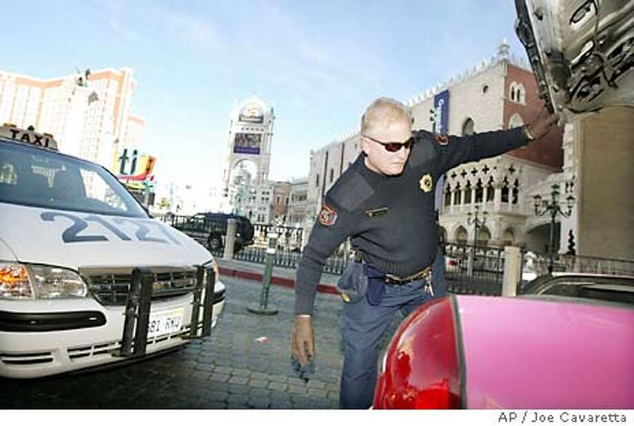 "William Silvey, security officer for the Venetian Hotel and Casino checks the trunk of a car entering the parking garage Monday, Dec. 22, 2003 on the Las Vegas Blvd. ""strip."" As the terror threat level is raised, most Las Vegas resorts are taking precautions such as searching cars entering the properties.(AP Photo/Joe Cavaretta) Security guard William Silvey checks the trunk of a car entering a casino parking garage in Las Vegas. Photo: JOE CAVARETTA"