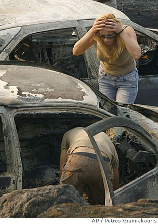 A relative reacts next to damaged cars in Artemida village near Zaharo, 330 kilometers (206 miles) southwest of Athens on Saturday, Aug. 25, 2007. The death toll from forest fires that raged uncontrolled across vast swathes of southern Greece for a second day increased Saturday to 37 people, and the casualties were believed to include several children, the fire department said. At least 30 of the deaths occurred in the western Peloponnese near the town of Zaharo, the department said. A massive fire in the area, fanned by strong winds, continued to burn out of control. (AP Photo/Petros Giannakouris) Photo: PETROS GIANNAKOURIS