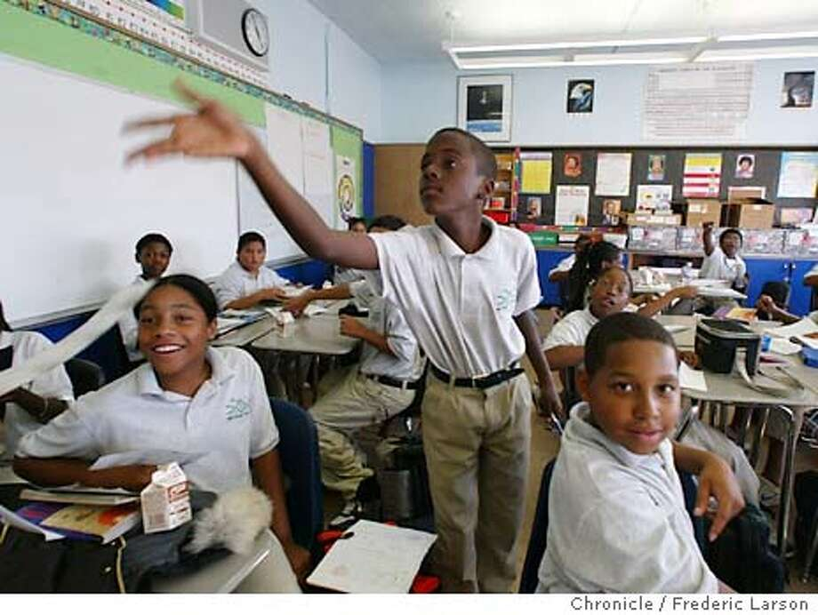 "KIPP_001_fl.jpg; At Will Chavarin math and science class at the KIPP Bridge Academy in Oakland sixth grade student Tony Shaver (center) gets his ""paycheck"" the encourage good behavior. Students (left) Olivia William (10) and Andre Turner (11) watch Tony get his reward. FREDERIC LARSON / The Chronicle Photo: FREDERIC LARSON"
