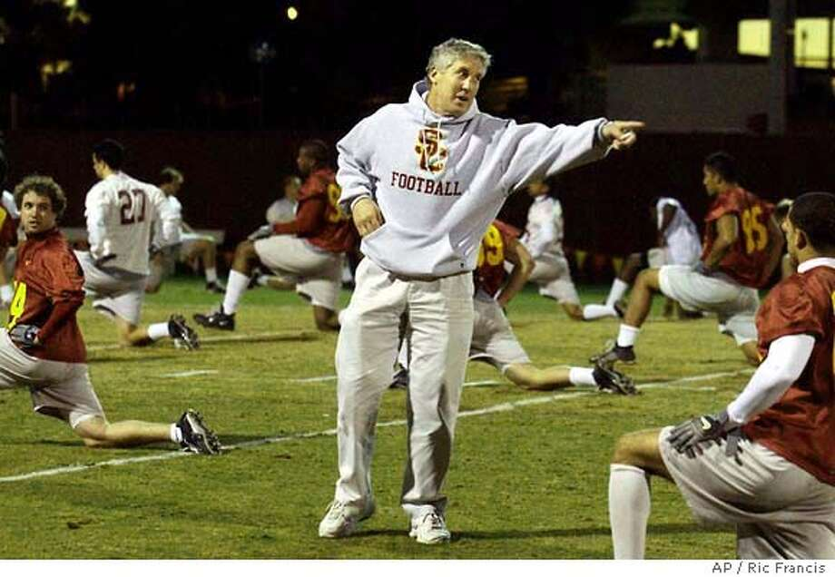 Southern California football coach Pete Carroll, center, gives instructions to a player during warmups before practice Monday, Dec. 8, 2003, in Los Angeles. USC will play Michigan at the Rose Bowl on January 1st. (AP Photo/Ric Francis) Pete Carroll's ability to convey his joie de vive to others has translated into top recruiting classes for USC. Pete Carroll's ability to convey his enthusiasm to others has translated into top recruiting classes for USC. Photo: RIC FRANCIS