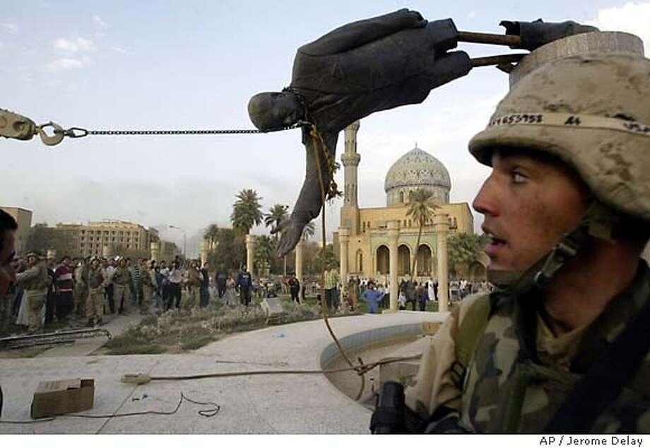Iraqi civilians and U.S. soldiers pull down a statue of Saddam Hussein in downtown Baghdad Wednesday April 9, 2003. (AP Photo/Jerome Delay) Photo: JEROME DELAY