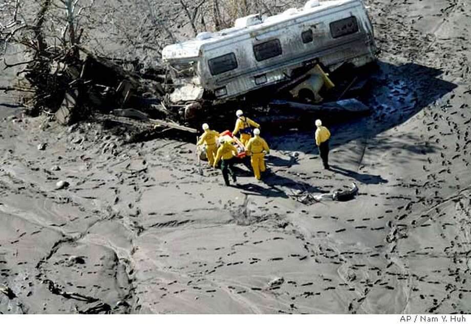 ** RETRANSMITTING TO CORRECT SPELLING OF CITY TO SAN BERNARDINO **Rescue workers search for victims Friday, Dec. 26, 2003, in a mobile home that was washed away after devastating mudslides swept through Devore, Calif., in the San Bernardino mountains on Thursday. (AP Photo/Nam Y. Huh) Photo: NAM Y HUH