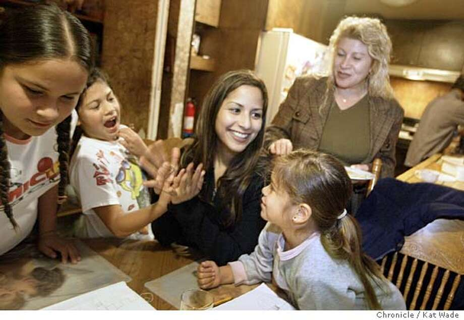 EBLATINA_0173_KW.jpg  On 12/3/03 Ruby Lopez, 23, (CENTER) 2003 Miss Latina USA, spends time playing finger string games with her little cousins (L TO R) Adekine, 12, Angie,8, and Alex Michel, 7, who live with her and her parents Lucy and Ismael Lopez in their Livermore home. Kat Wade / The Chronicle Photo: Kat Wade