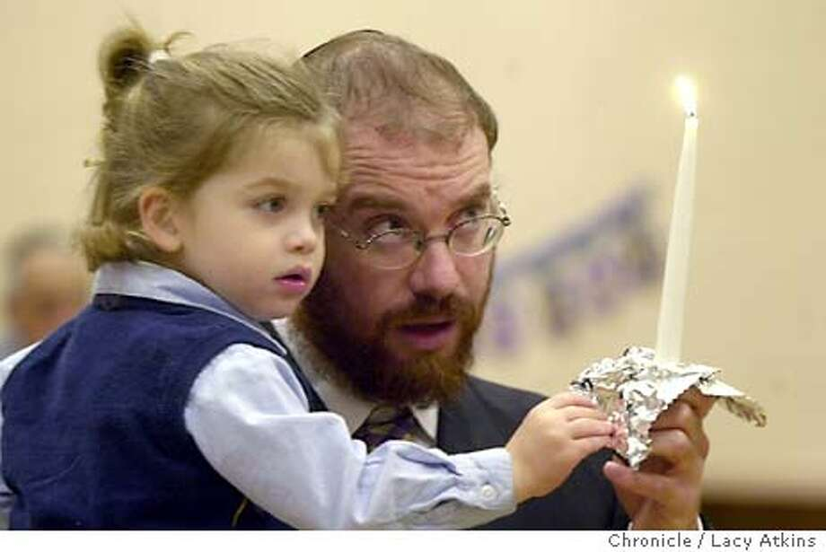 KABBALH_002_LA.jpg  Rabbi Shlomo Zarchi holds his son Yaakov Meir, 2yrs, as he lights the first candle for Hannukah, Friday Dec. 19,2003 in San Francisco.Rabbi Shlomo Zarchi teaches a class through the JCC in Kabbalh. Lacy Atkins / The Chronicle Photo: Lacy Atkins