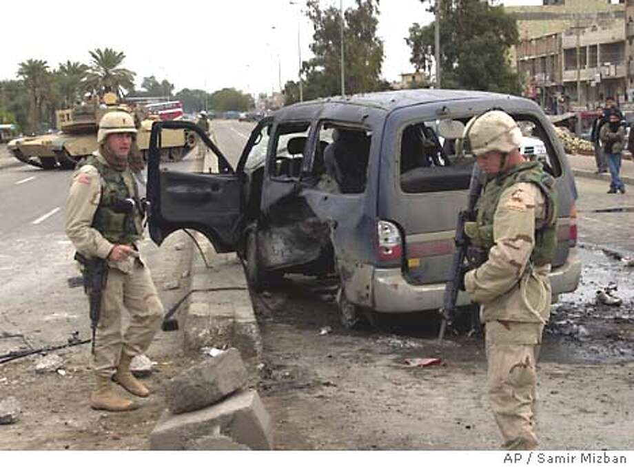 U.S. soldiers inspect a minibus damaged in a blast after a roadside explosive device went off killing two and wounding two people in central Baghdad Wednesday, Dec. 24, 2003.( AP Photo/ Samir Mizban ) Photo: SAMIR MIZBAN