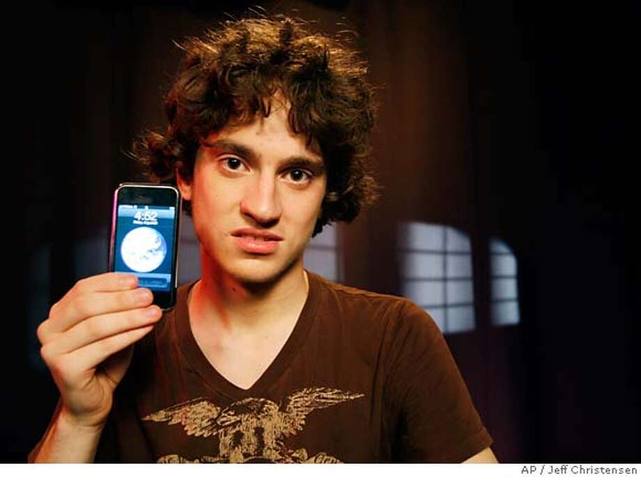 George Hotz, 17, holds an iPhone that he has unlocked and is using on T-Mobile's network, Friday, Aug. 24, 2007 in New York. Hotz has broken the lock that ties Apple's iPhone to AT&T's wireless network, freeing the most hyped cell phone ever for use on the networks of other carriers, including overseas ones. (AP Photo/Jeff Christensen) Photo: Jeff Christensen