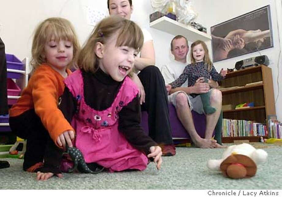 SOSLOVEJOY_005_LA.jpg  Holly Lovejoy plays with her sister Nina with her mother Vanessa, and father Clive and Amder watching on, at their apartment in San Francisco, Thursday Dec.18, 2003. Holly Lovejoy is a 4-year-old triplet who has cerebral palsy and her sisters Nina and Amber.Thanks to therapy, she attends a regular preschool with her two sisters. Holly's parents,Vanessa and Clive, learned about a therapeutic tricycle that is not only fun to ride, but will also help strengthen her legs,Dec.18, 2003 in San Francisco.  Lacy Atkins / The Chronicle Photo: Lacy Atkins