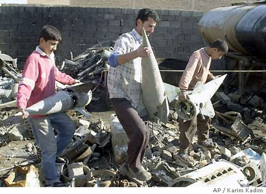 Iraqi workers carry empty Russian-made Sam 7 missile heads before melting them for scrap iron in Falluja, northeastern Iraq, Monday Dec. 22, 2003. (AP Photo/Karim Kadim) Photo: KARIM KADIM