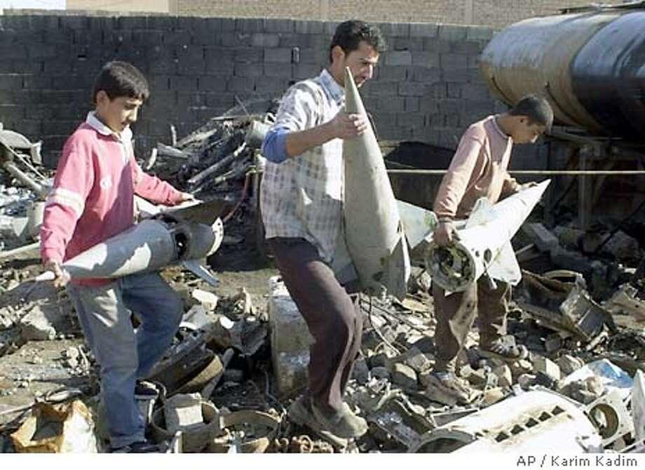 Iraqi workers carry empty Russian-made Sam 7 missile heads before melting them for scrap iron in Falluja, northeastern Iraq, Monday Dec. 22, 2003. (AP Photo/Karim Kadim) Photo: KARIM KADIM